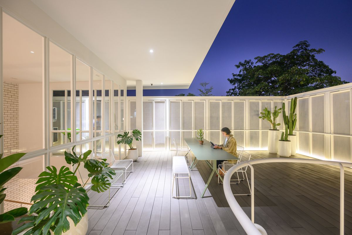 Illuminated terrace with table and plants.