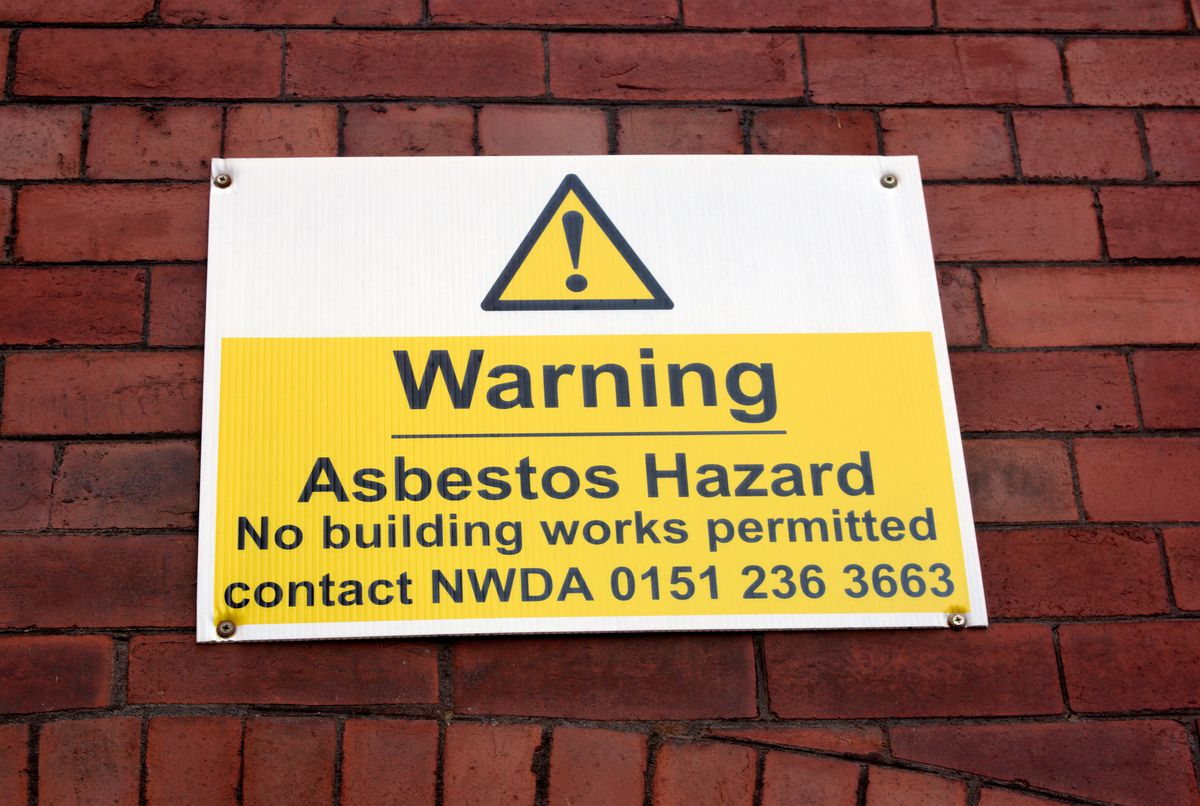 Warning asbestos hazard sign on old mill in Ancoats, East Manchester UK