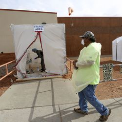 Ronnie Blackwater prepares to tape a triage tent closed outside of the Monument Valley Health Center in Oljato-Monument Valley, San Juan County, after testing for COVID-19 ended on Thursday, April 16, 2020.