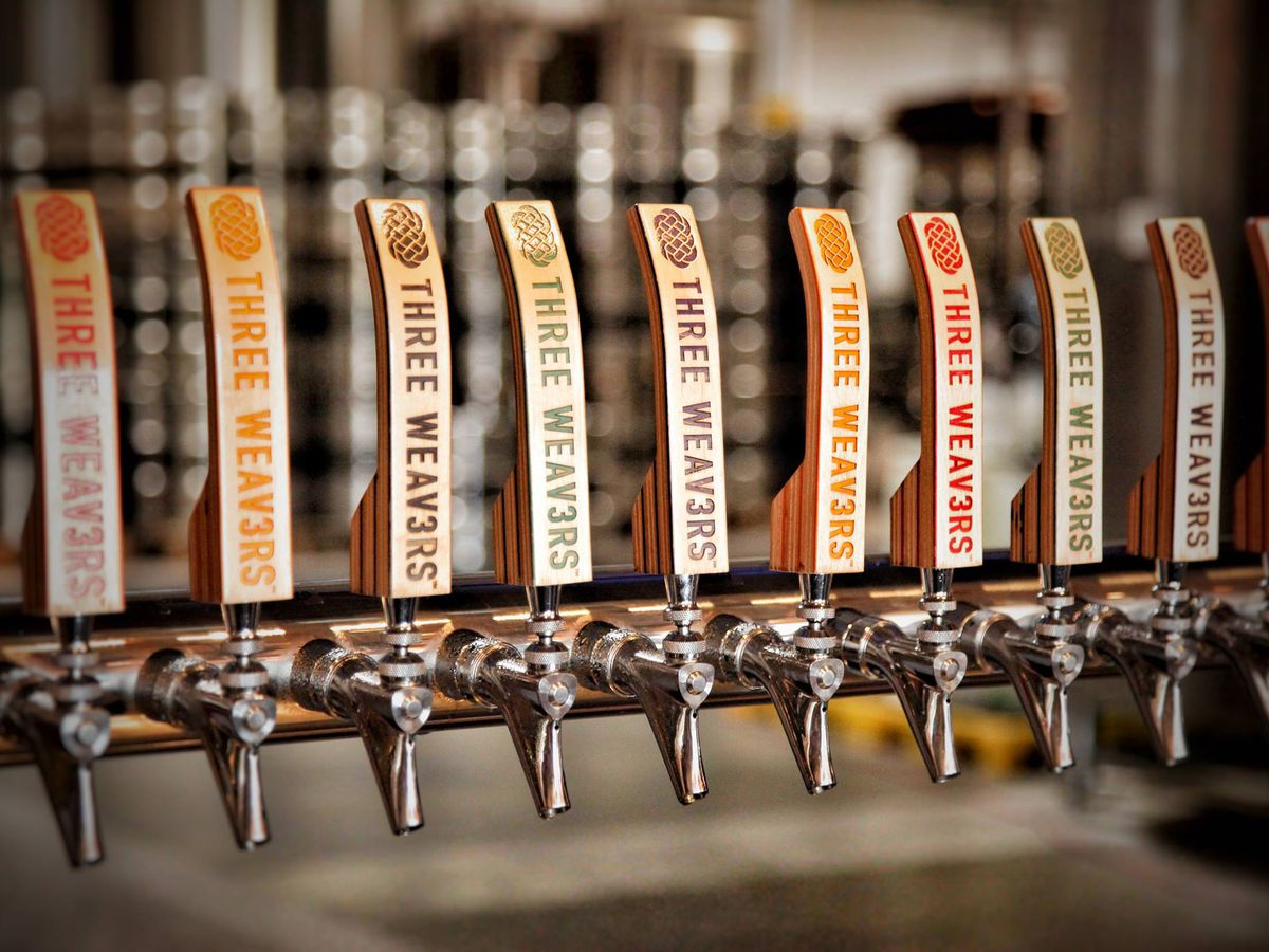 A lineup of wooden craft beer taps from Three Weavers Brewing.