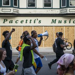 Protesters march by boarded up businesses in Kenosha on the second night of unrest after police shot Jacob Blake, Monday night, Aug. 24, 2020.