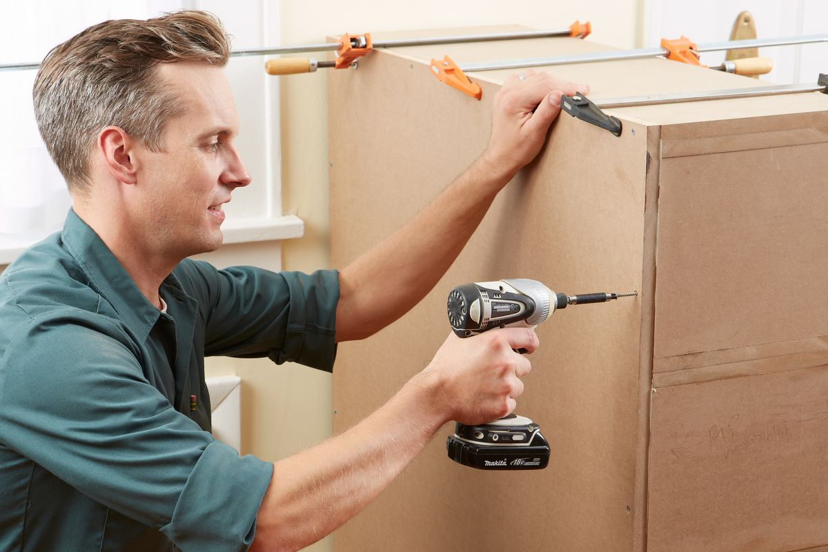 Man Attaches MDF Panel On Back Of Stack Of Columned Room Divider