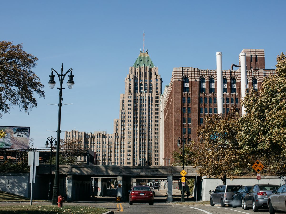 A road leads through an underpass in the foreground. In the background, there's a tall brick building with white brick stripes and an even taller stone building with two towers.
