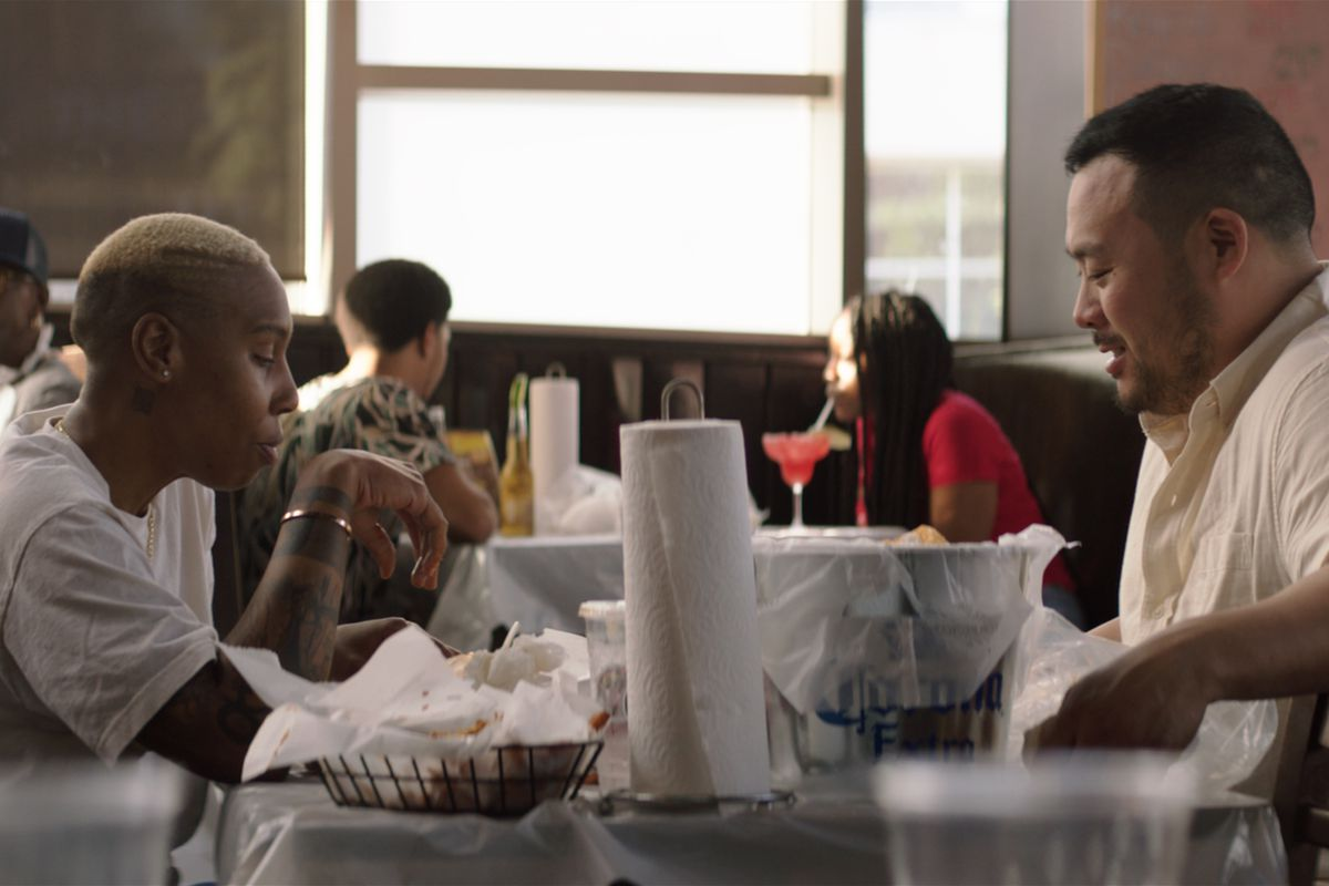 Lena Waithe and David Chang seated at a restaurant table loaded with paper towels and spicy seafood.