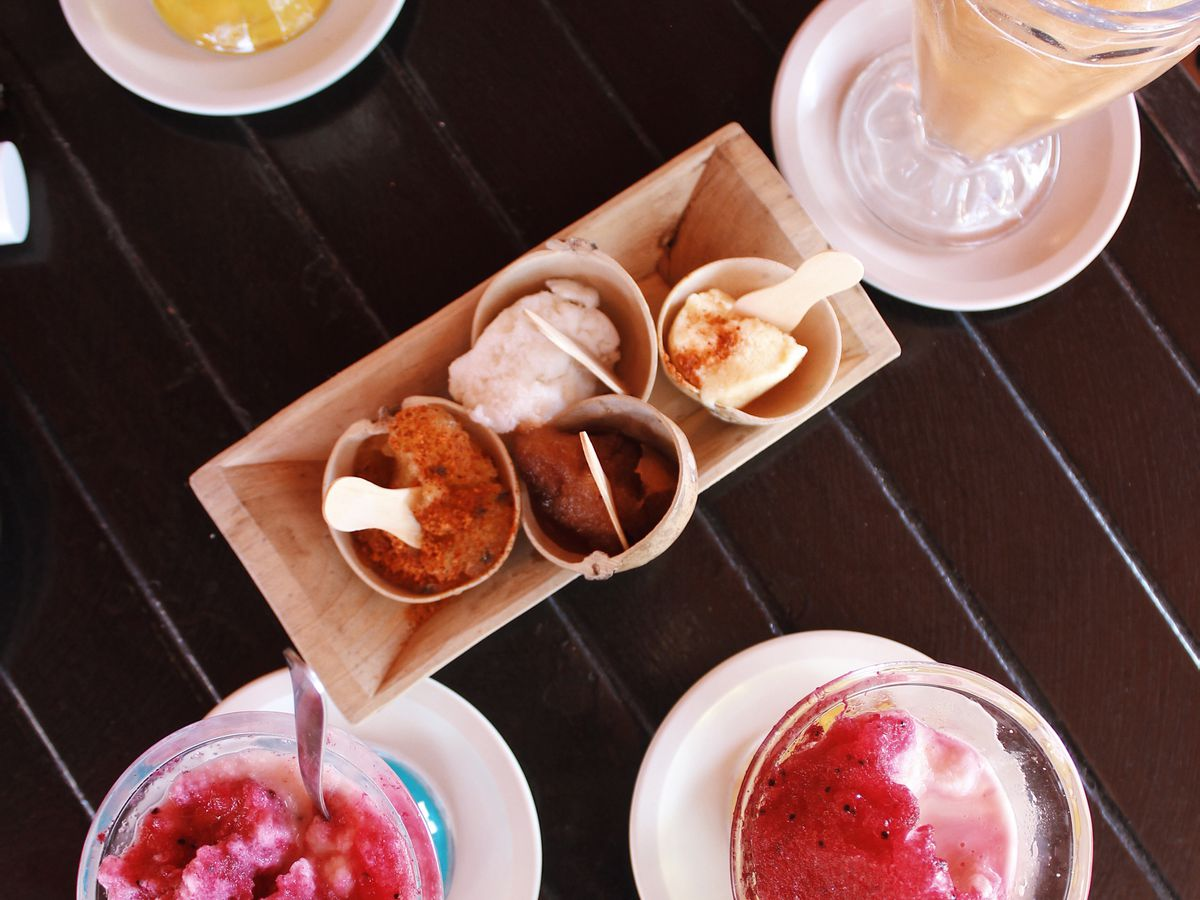 several pink-topped ice treats sit on a table.
