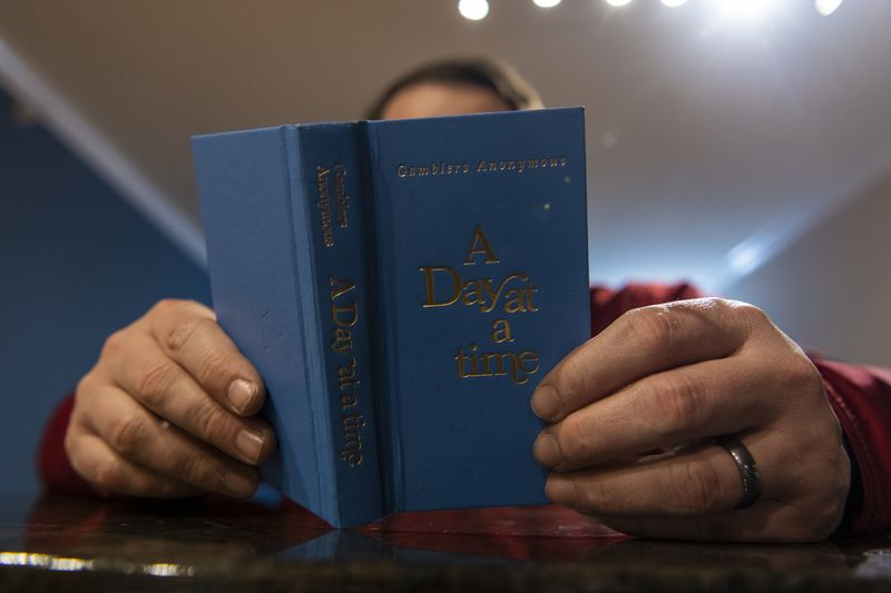 A recovering sports gambling addict reads his favorite passages from 'A Day at a Time' a book by Gamblers Anonymous last month.