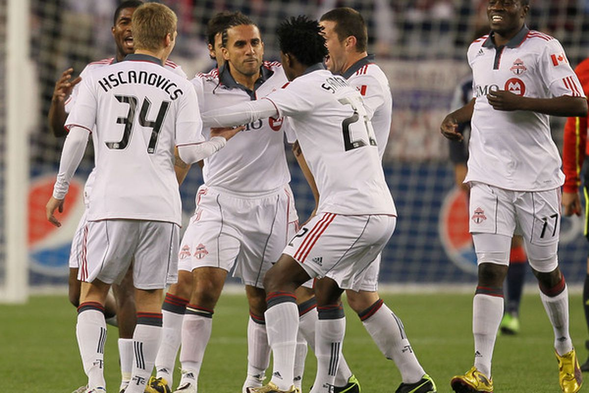 Toronto players try their best to stop their teammate Dwayne De Rosario from doing his stupid dance