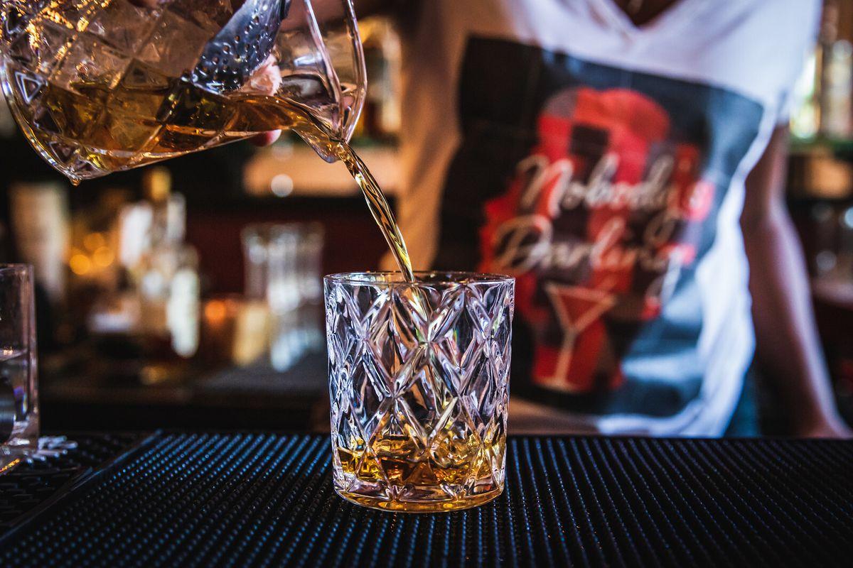 A bartender pours brown liquor into a fancy rocks glass