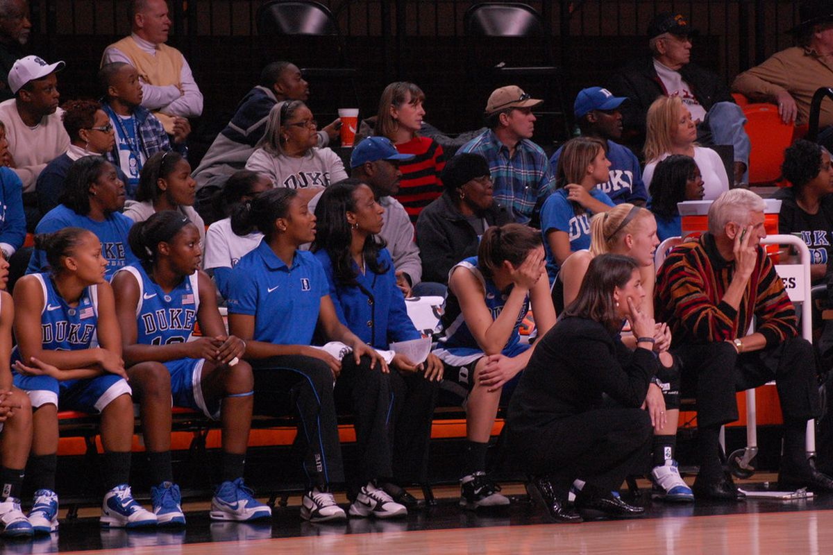 Duke bench looks on intently during Oklahoma State shellacking - others look on intently too; Tulsa Shock head coach/GM Nolan Richardson and assistant Wayne Stehlik in top left corner