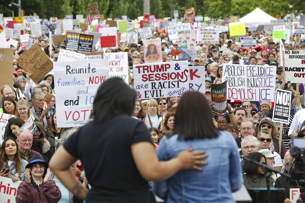 Monserrat Padilla, left, puts her arm around Aurora, an undocumented immigrant, as Aurora speaks to several thousand demonstrators gathered outside the Federal Detention Center in SeaTac to protest the separation of families crossing the U.S.-Mexico borde