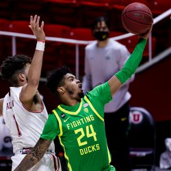 Oregon Ducks guard Aaron Estrada (24) goes to the hoop ahead of Utah Utes forward Timmy Allen (1) during the game at the Huntsman Center in Salt Lake City on Saturday, Jan. 9, 2021.