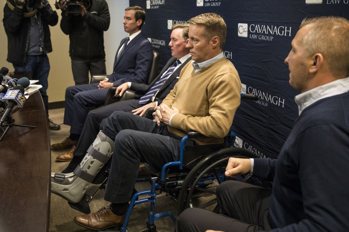 Attorney Tim Cavanagh (left) and Tomasz Stacha (right) look on as John Sherwood speaks to reporters about his injuries, including a broken ankle, during a press conference Nov. 1, 2018. Stacha and Sherwood have filed a lawsuit alleging they were beaten by off-duty Chicago Police Sgt. Eric Elkins.