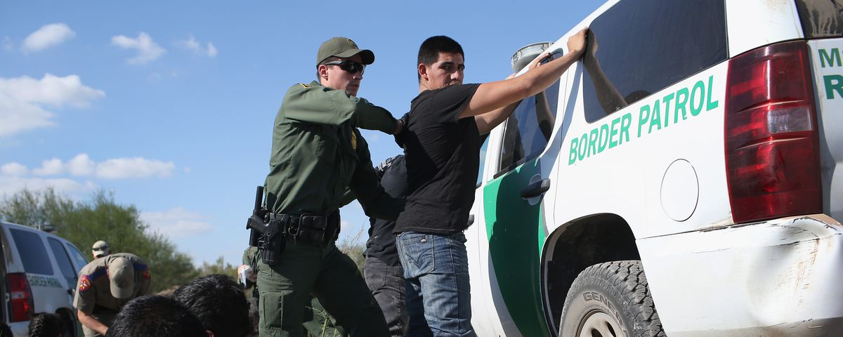 A US Border Patrol officer body searches an undocumented immigrant after he illegally crossed the U.S.-Mexico border and was caught near Rio Grande City, Texas