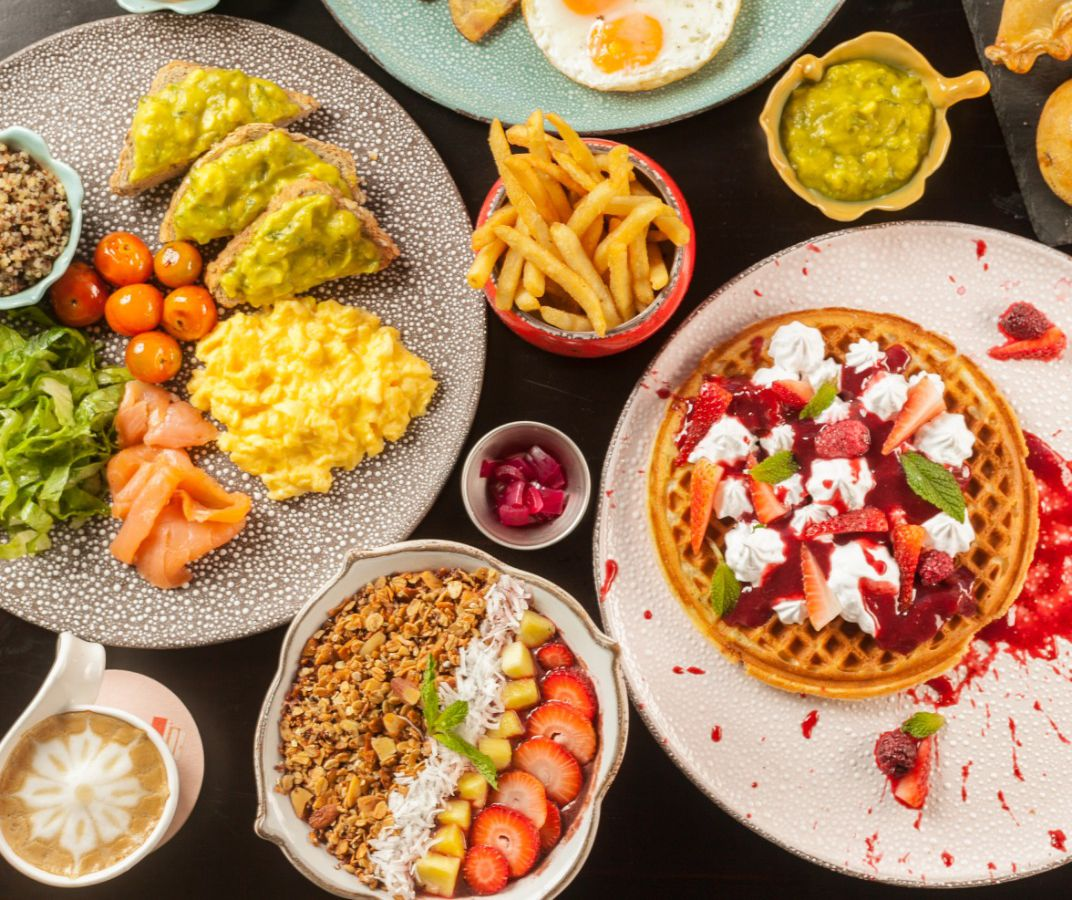 From above, a number of breakfast dishes including a waffle topped with whipped cream and fruit slices, avocado toast with scrambled eggs, a bowl of granola and fruit, and french fries