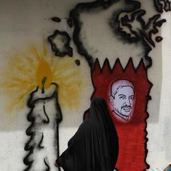 A Bahraini woman looks at an image of jailed hunger striker Abdulhadi al-Khawaja painted on a map of Bahrain on a wall in Barbar, Bahrain, west of the capital of Manama, on Monday, April 30, 2012. A defense lawyer says a Bahrain appeals court has ordered the reexamination of the case of al-Khawaja and more than a dozen others.