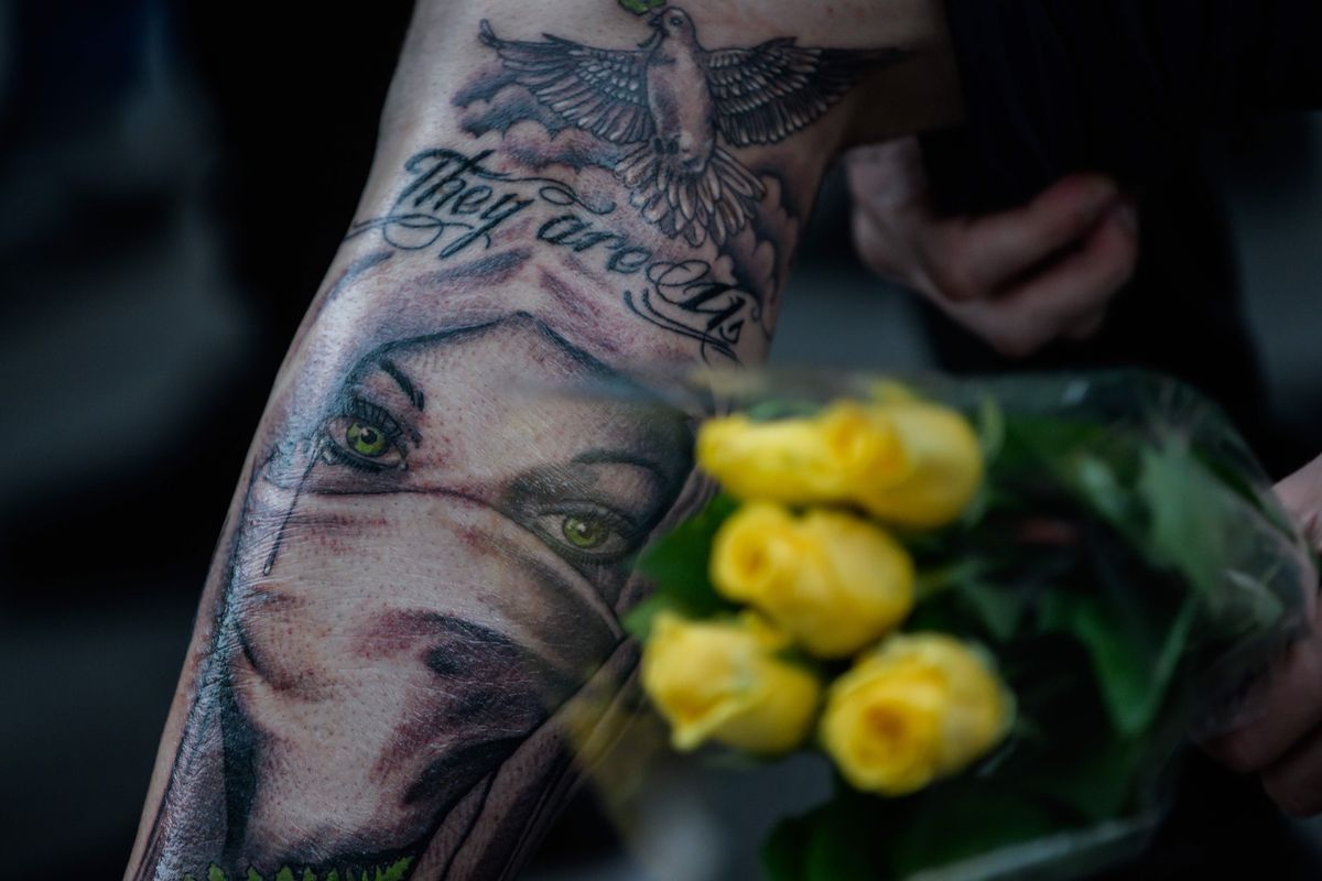 Ex-gang member Jacob Leo Skilling, 26, shows his freshly imbedded tattoo of the face of a Muslim woman wearing a face veil with the words' They are us after the haka was performed by biker gang members in front of a gathering of people as a tribute to victi