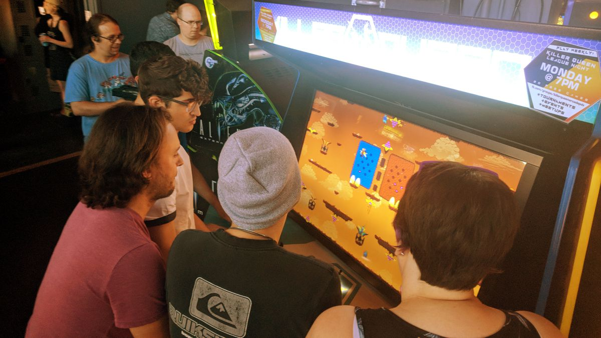 killer queen arcade machine being played by a crowd, portland