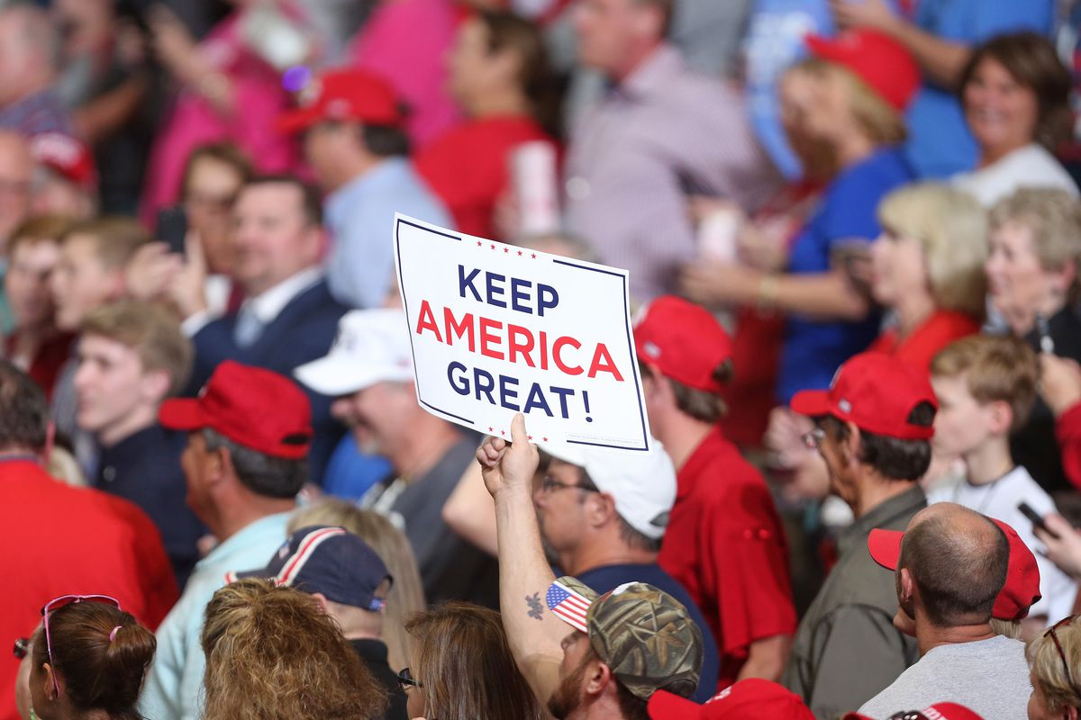 """A Trump supporter at a rally holds up a """"Keep America Great"""" sign."""