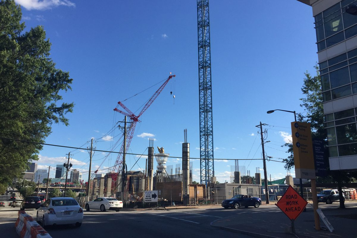 Two tower cranes stand in a field of concrete columns.