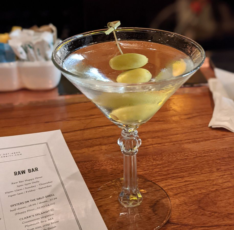 Olive-garnished martini with a menu in background