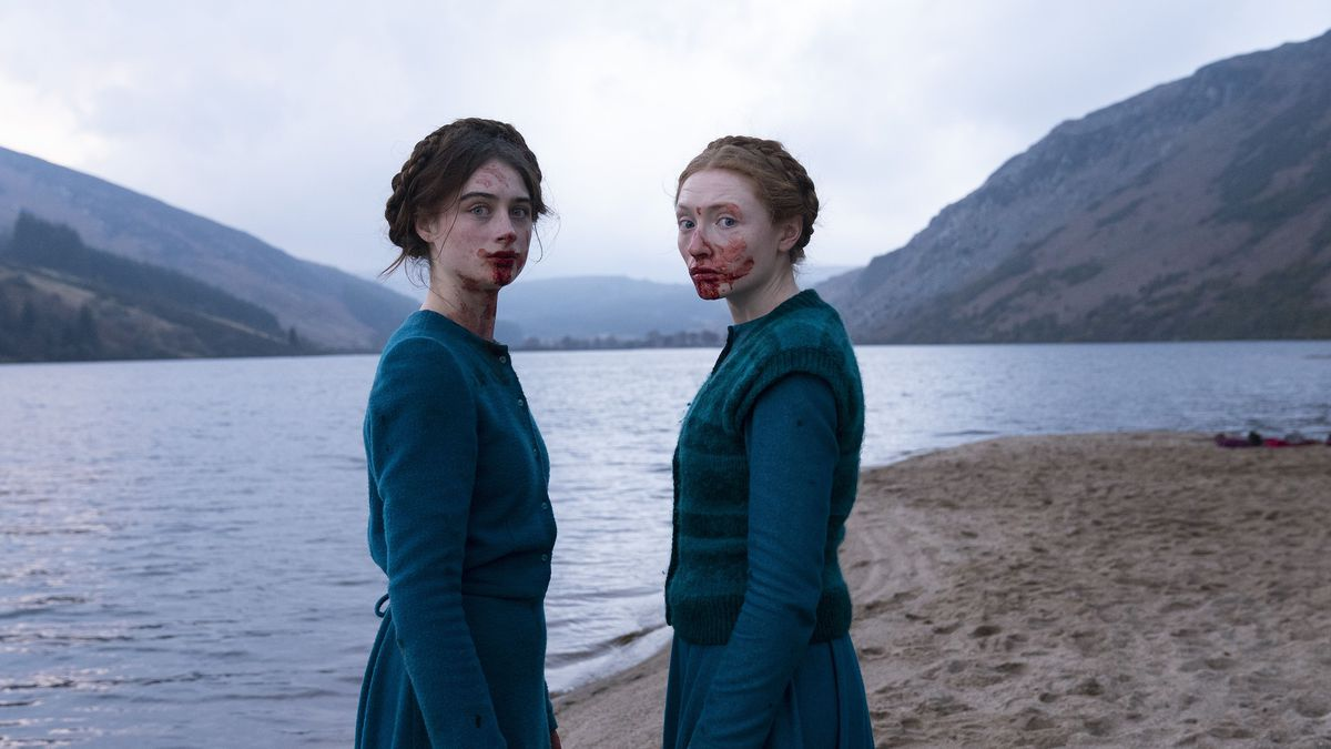 two girls dressed in blue, with blood on their faces