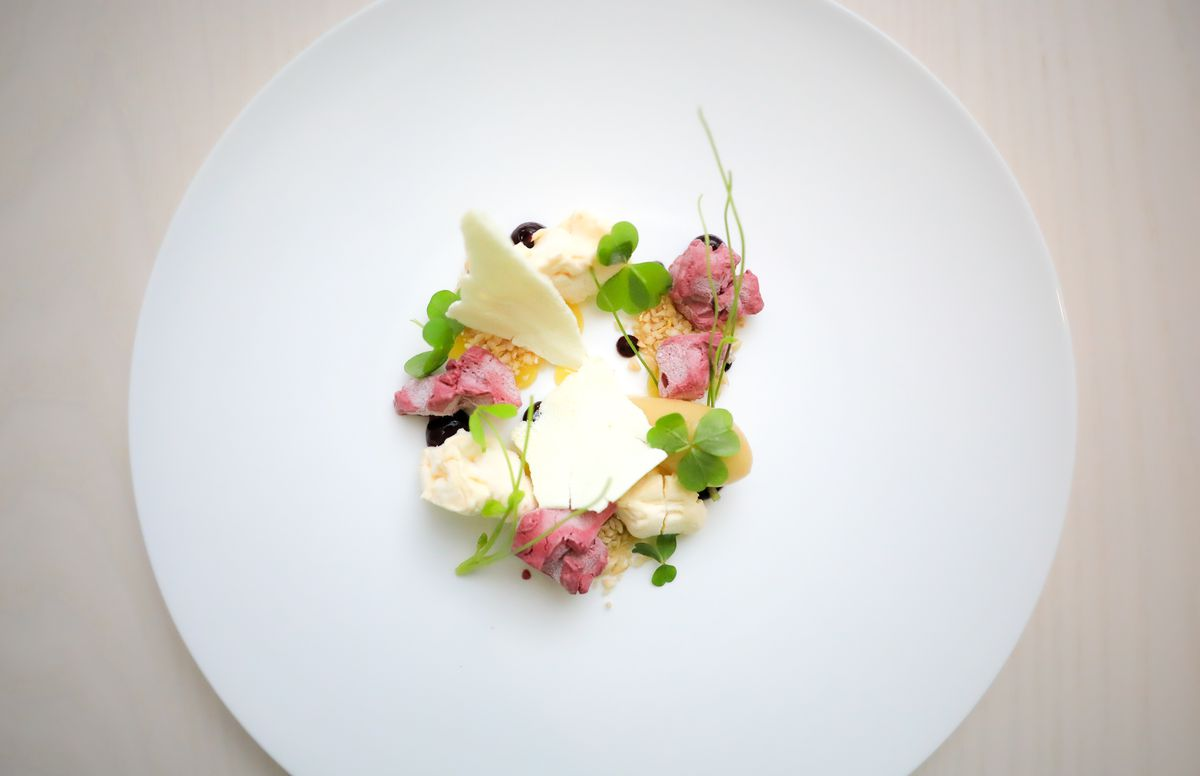 A white plate with a salad of chamomile, pine nut, black raspberry, and oxalis