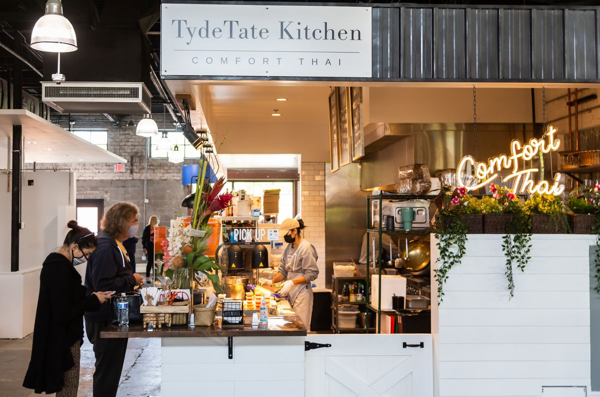Two people wait for their order from TydeTate Kitchen stall at Chattahoochee Food Works in Atlanta