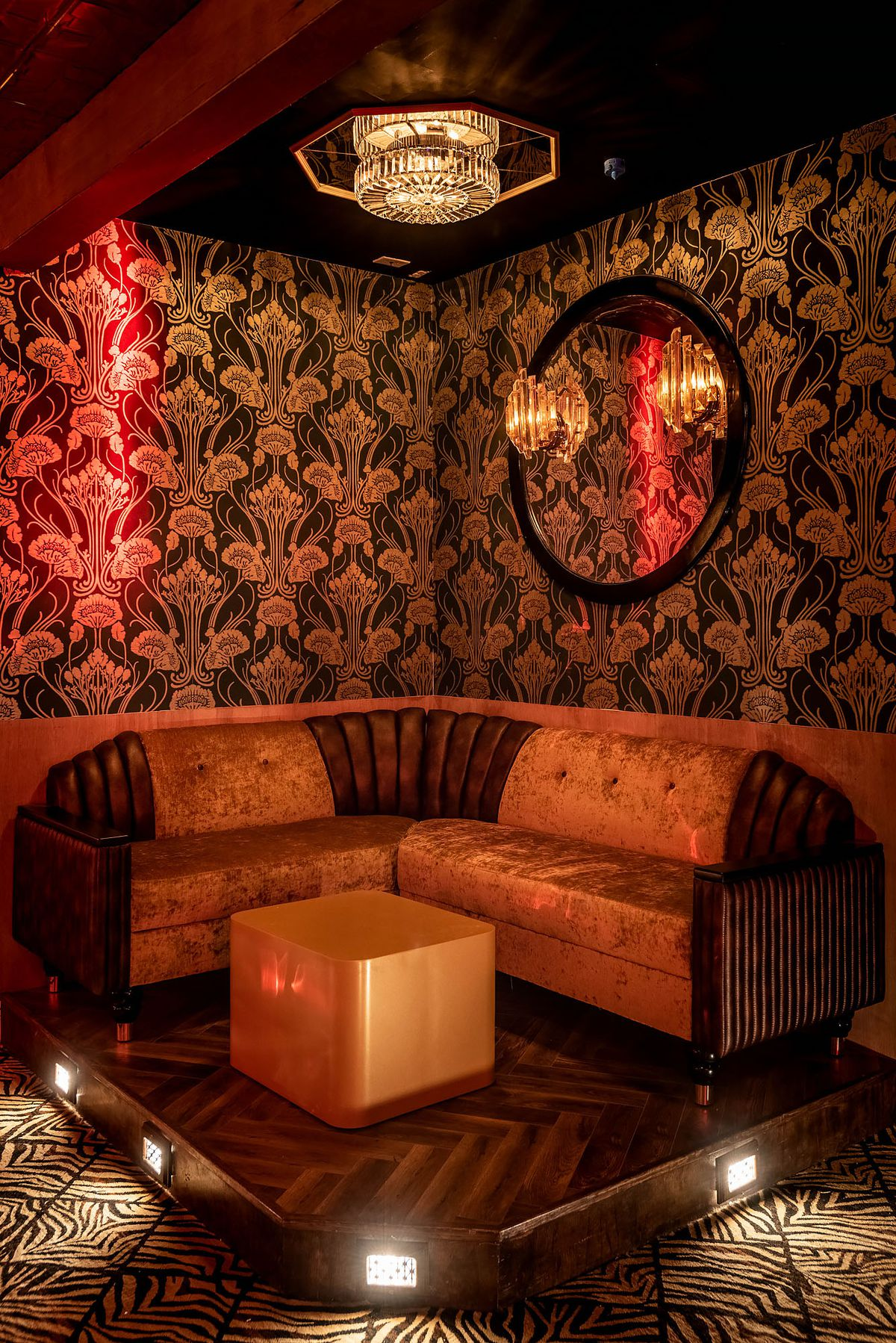 Lounge seating with textured wallpaper and ottoman.