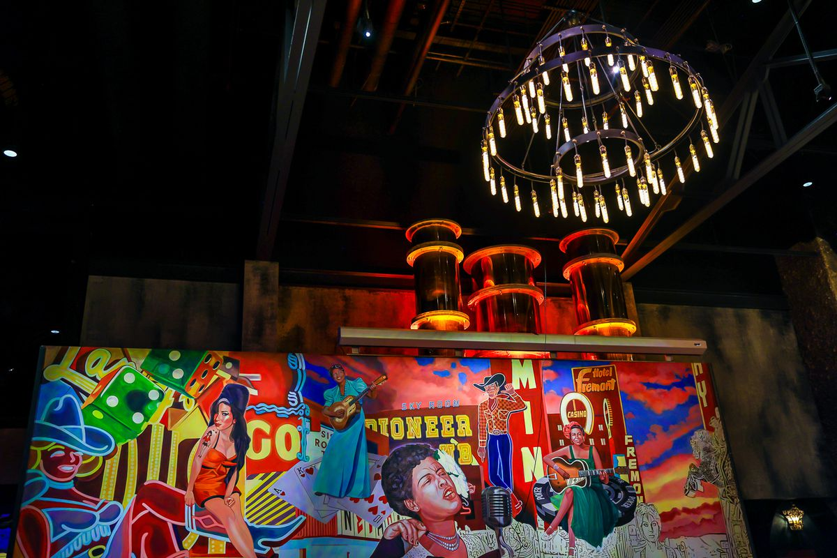 A colorful mural with chandeliers on either side.
