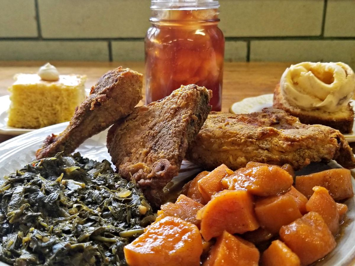 A paper plate of fried chicken pieces with piles of collards and yams, with a Mason jar of iced tea and a piece of conrbread in the background
