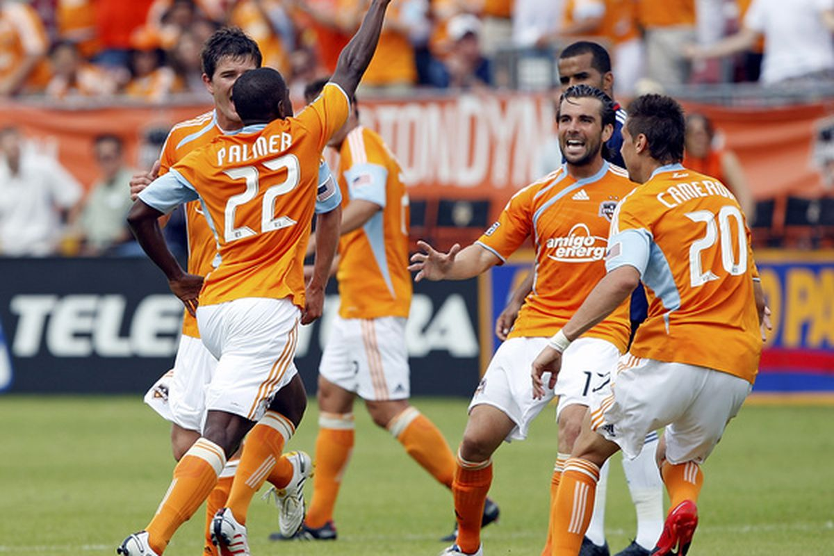 HOUSTON - APRIL 17:  Lovel Palmer #22 celebrates with Mike Chabala #17 and Geoff Cameron #20 after scoring in the first half against Chivas USA at Robertson Stadium on April 17, 2010 in Houston, Texas.  (Photo by Bob Levey/Getty Images)