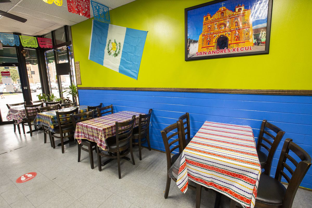 A restaurant dining room with tables covered in striped Guatemalan tablecloths. The top half of the wall is neon green and the bottom is blue. A Guatemalan flag hangs on the wall beside a photo of a multicolored church