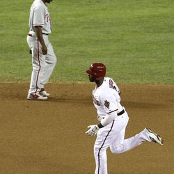 Arizona Diamondbacks' Justin Upton, right, rounds the bases after hitting a home run as Philadelphia Phillies' Jimmy Rollins looks down during the fourth inning of a baseball game Monday, April 23, 2012, in Phoenix.
