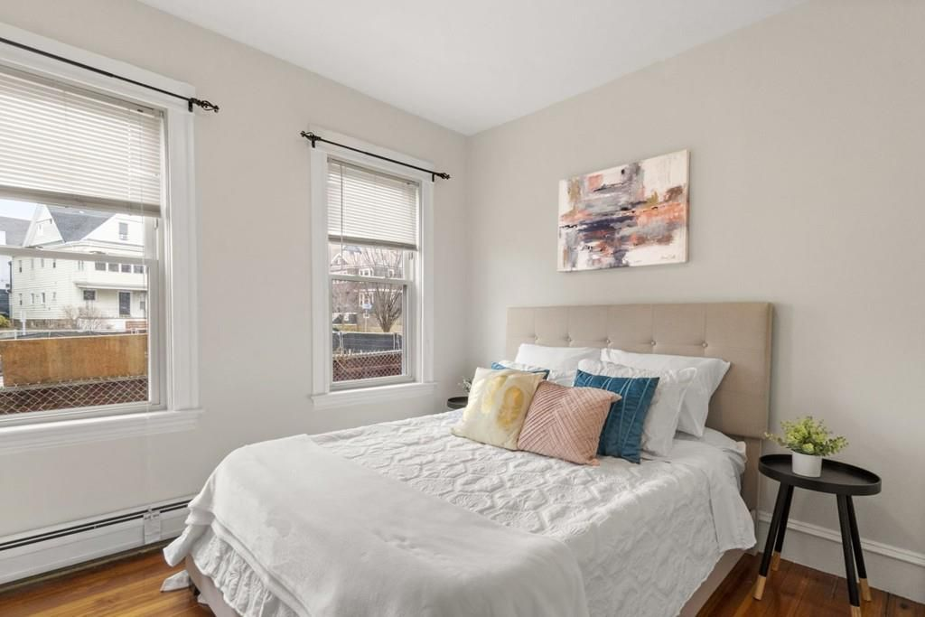 A bedroom with a bed next to two windows.