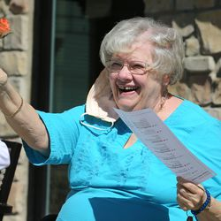 Sharon Hansen smiles and waves her rose as her family passes by residents at The Ridge Cottonwood senior living center in Holladay. Family members displayed signs, balloons and waves for a Mother's Day parade on Saturday, May 9, 2020.