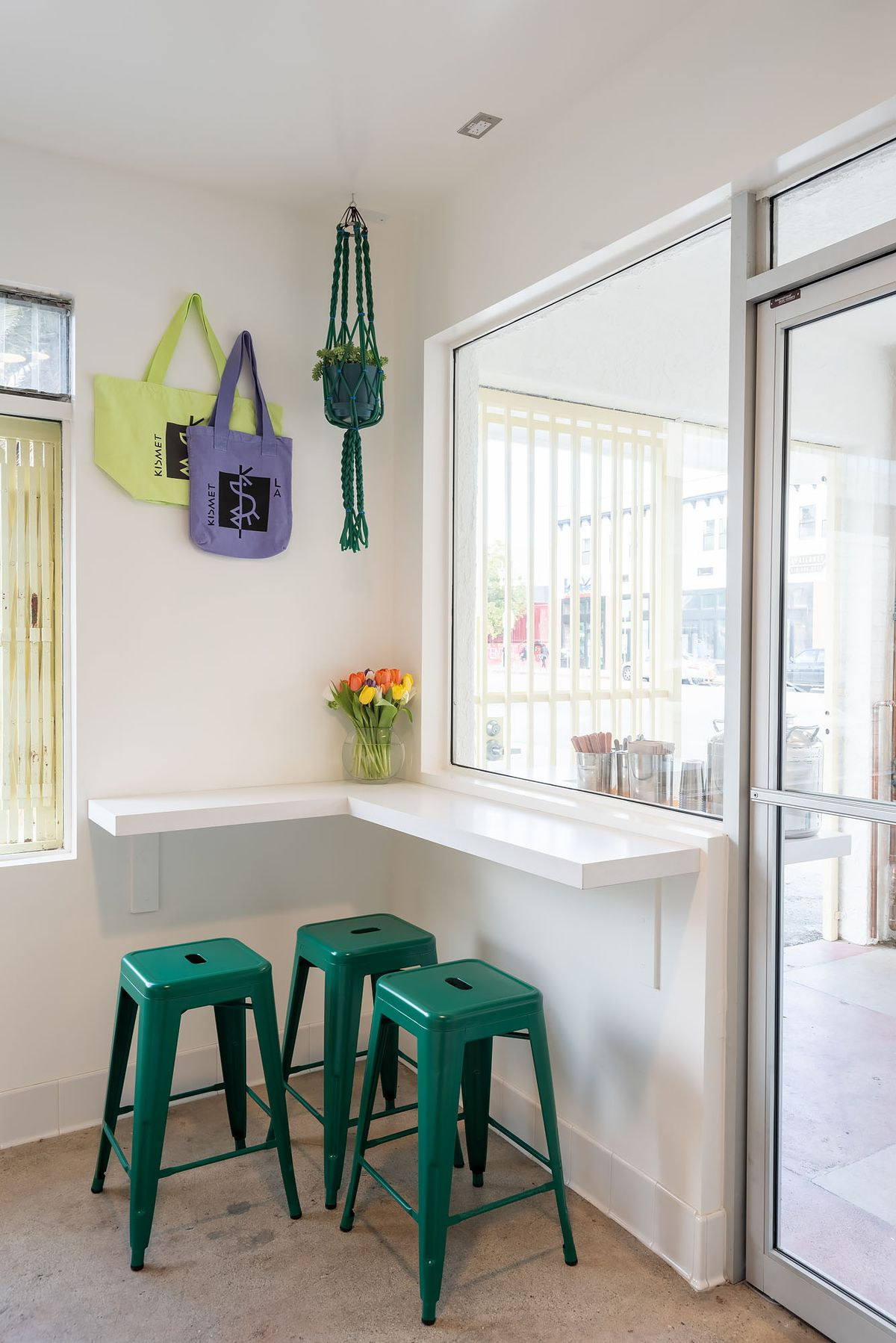 Tote bags and plants and green stools inside a small new white-painted restaurant.
