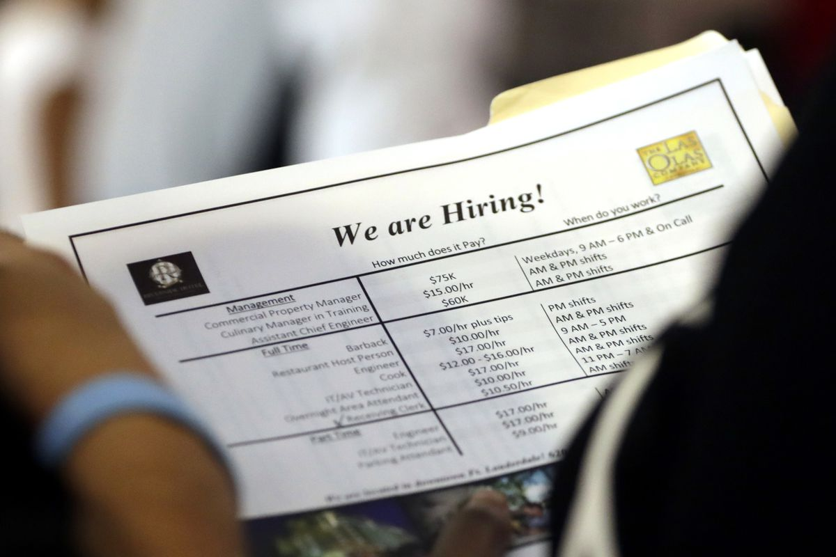 In this June 2018 photo, a job applicant looks at job listings for the Riverside Hotel at a job fair hosted by Job News South Florida in Sunrise, Florida.