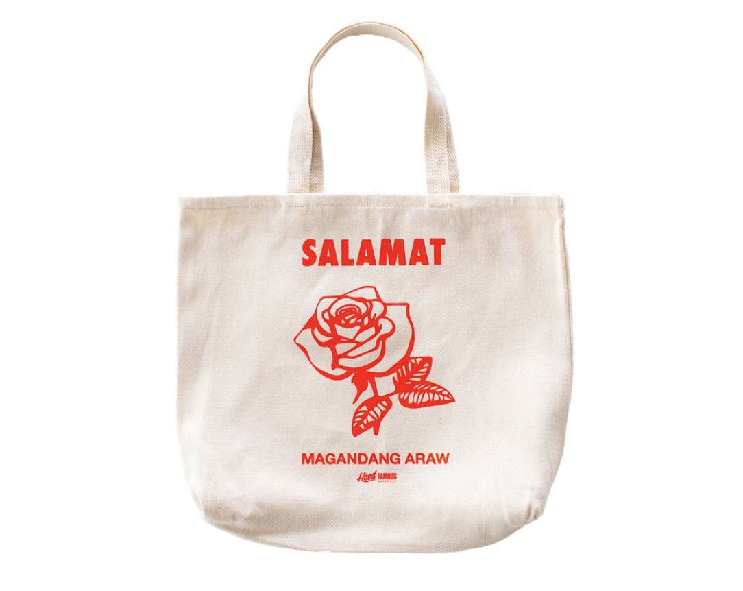 """A white tote with a flower on the front and the word """"Salamat"""" in large lettering, """"Magandang araw"""" in smaller lettering below"""