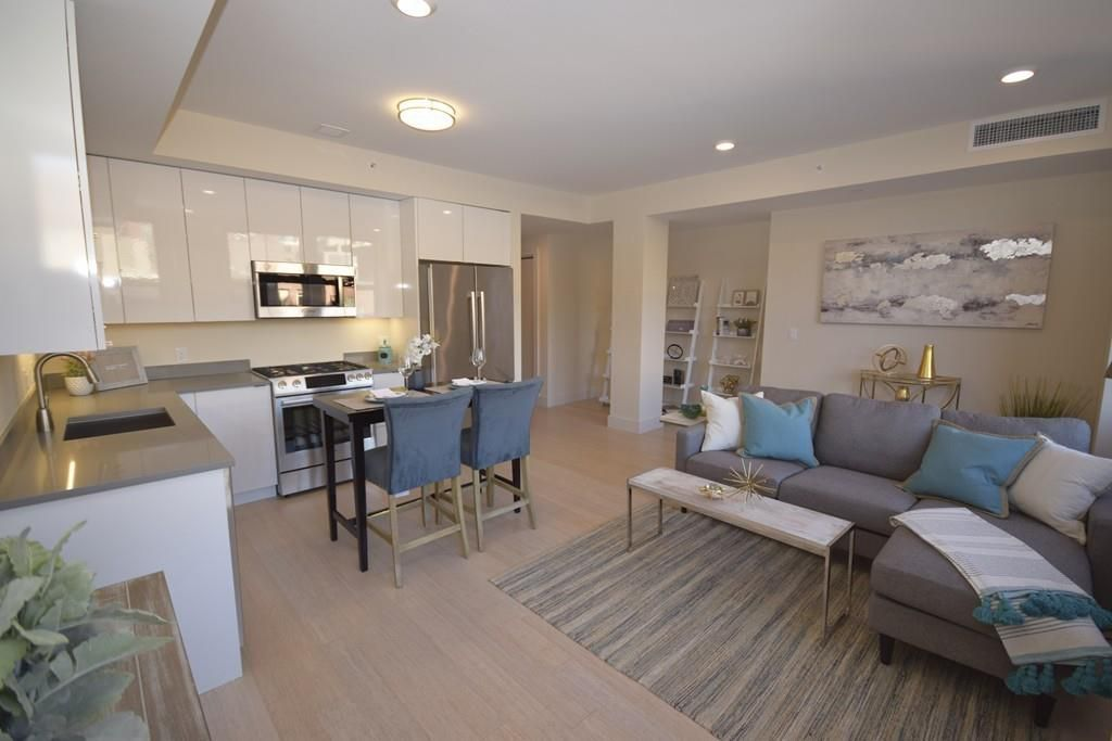 A spacious and open living room-dining room-kitchen area with furniture.