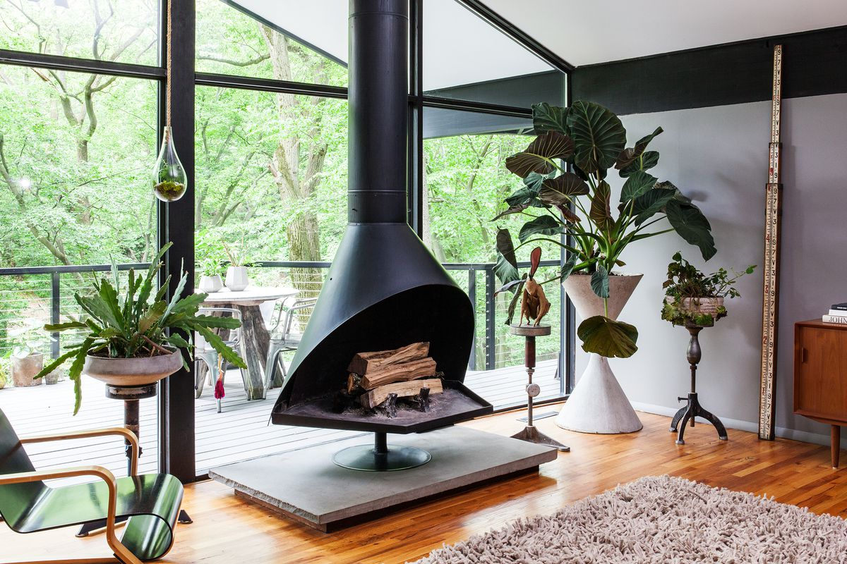 A black, metal fireplace is directly in front of huge windows that look out on a small forest.