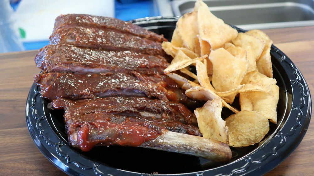 saucy ribs and potato chips are served on a black plastic plate