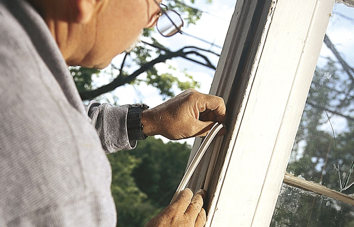 Person adding weatherstripping to a door to seal a gap.