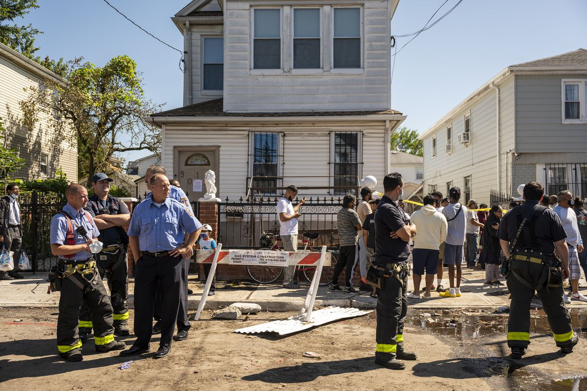 Responders and neighbors in front of 90-11 183rd Street in Queens. Flooding from Hurricane Ida drowned two people in the basement of this home in Hollis, Queens. Sept. 2, 2021.