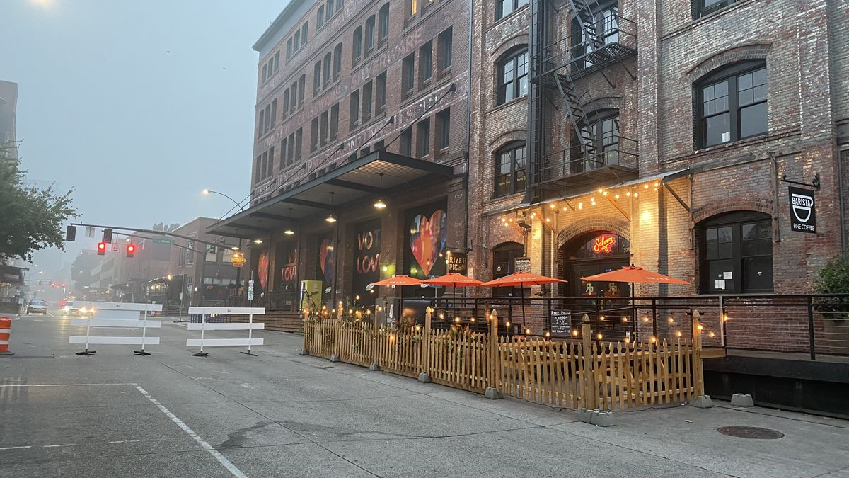Tall brick buildings are lined with outdoor lights, hanging over new outdoor seating areas within the Pearl District