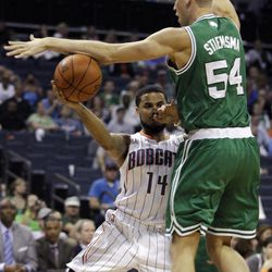 Charlotte Bobcats' D.J. Augustin (14) tries to pass the ball around Boston Celtics' Greg Stiemsma (54) during the first half of an NBA basketball game in Charlotte, N.C., Sunday, April 15, 2012.