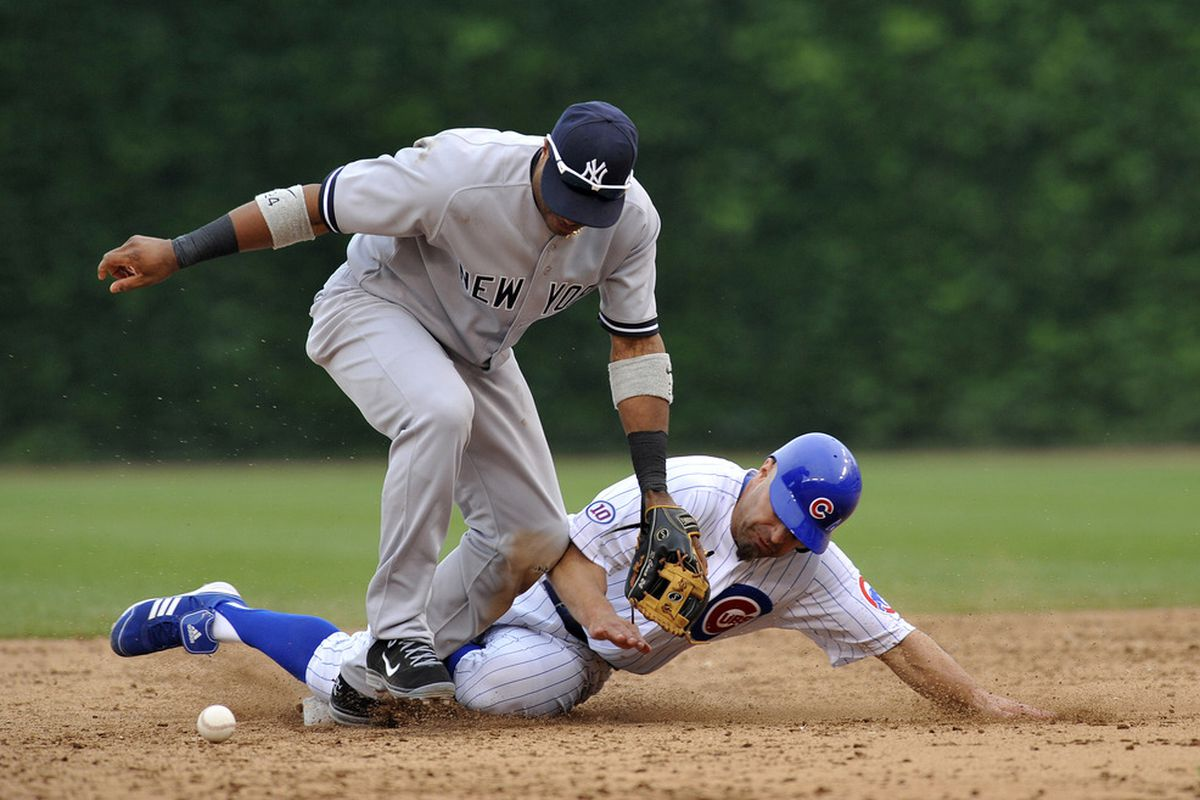 Reed Johnson of the Chicago Cubs is safe at second base as Robinson Cano of the New York Yankees drops the ball on June 18, 2011 at Wrigley Field in Chicago, Illinois.  (Photo by David Banks/Getty Images)
