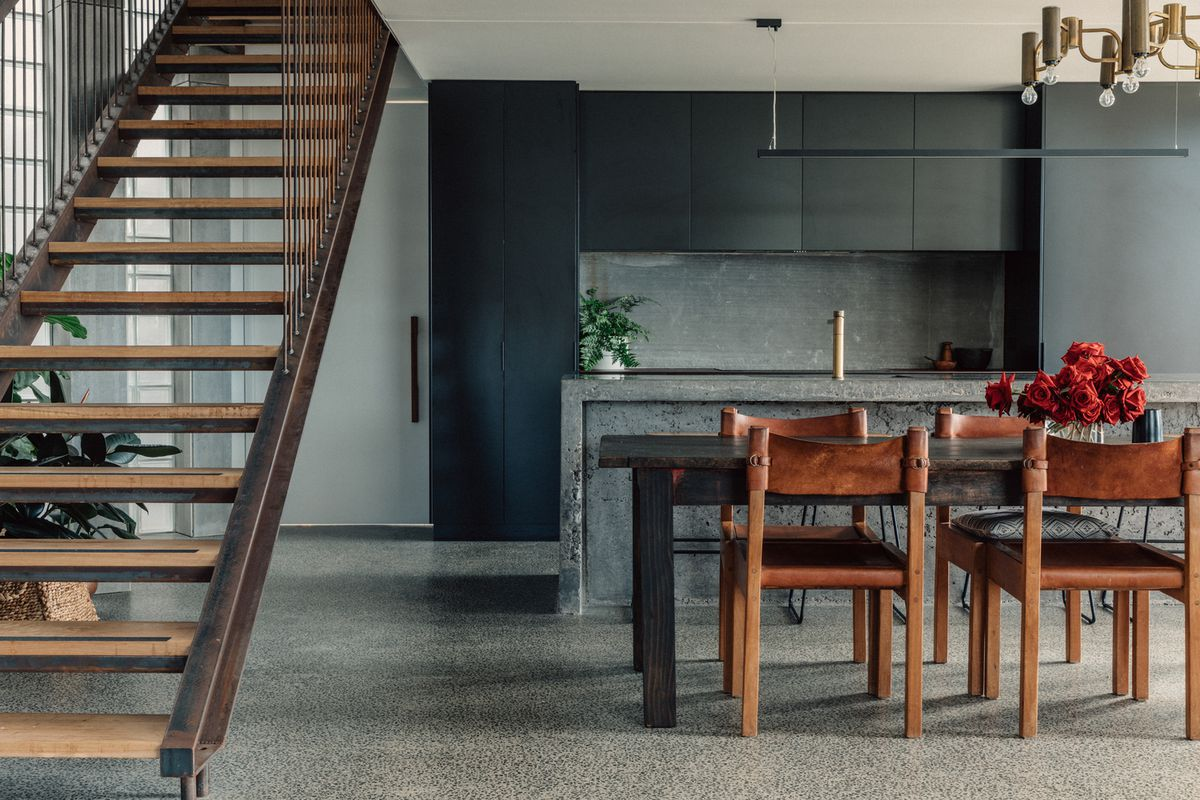 A kitchen has concrete floors, gray cabinets, concrete island, wooden dining table and chairs, and a floating staircase to an upper level.
