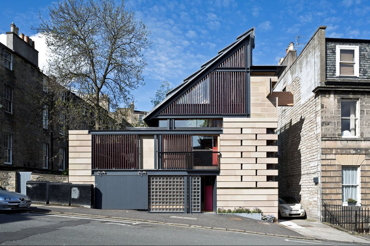 House with eclectic facade of stone, wooden slats, and glass bricks with dramatic sloping roof sits on a hill.