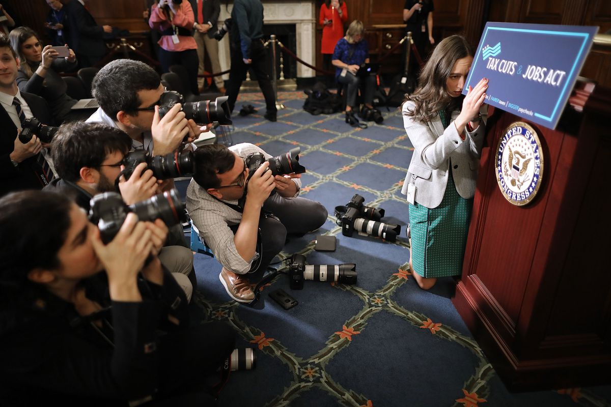 Paige Waltz, digital media coordinator for Speaker of the House Paul Ryan, preps the podium where a House vote will take place while photographers gather around with cameras.