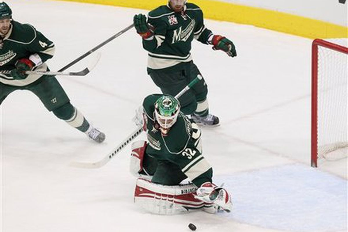 Minnesota Wild goalie Niklas Backstrom makes a save as teammates Clayton Stoner, left and Greg Zanon look on during the first period of an NHL hockey game against the Detroit Red Wings, Sunday, Feb. 20, 2011, in St. Paul, Minn.